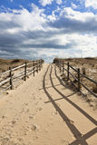 Sand Path Leading to Ocean. Sandy trail to the beach under blue sky with wispy clouds Stock Photography