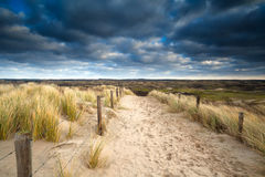 Sand path to dunes and cloudy sky Royalty Free Stock Photography
