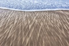 Sand patterns and wave on beach. Abstract closeup image of sand patterns left by a retreating wave on the beach at Pacific City on the Oregon Coast Royalty Free Stock Photo