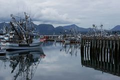 Sand Point Alaska Pier. Sand Point, Alaska Fishing Pier and harbor with reflections in water. September 1, 2018 stock images