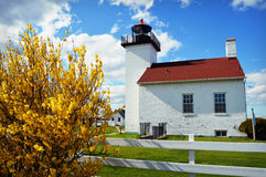 Sand Point Lighthouse. In Escanaba, Michigan with yellow forsynthia in bloom along the fence line Royalty Free Stock Photos