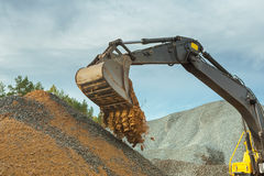 Sand pouring from scoop of excavator Stock Photos
