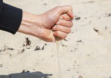 Sand pours from the hand of man. stock image