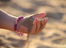 Sand pours out of the child hand. Brown sand pours out of the child hand Royalty Free Stock Photography