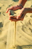 Sand pours out of the female hands. Horizontal Stock Photography
