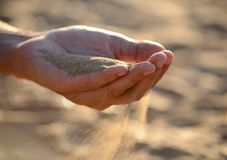 Sand pours out of the hands Stock Photos