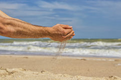 Sand pours from the palms, the sea and the beach Royalty Free Stock Photo