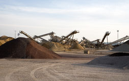 Sand Production. A view of a sand production site with heaps of sand, cranes and other machinery Royalty Free Stock Image