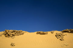 Sand with rocks under dark blue sky. Sand with rocks seen background under dark blue sky Royalty Free Stock Photo