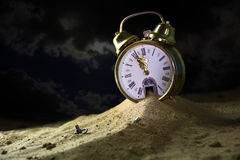 Sand running from a alarm clock in a fantasy desert at night,. Sand running down from the door of a alarm clock in a fantasy desert at night, surreal metaphor stock photos