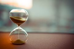 Sand running through the bulbs of an hourglass measuring the passing time in a countdown to a deadline, on a blur background with. Copy space royalty free stock photo