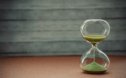 Sand running through the bulbs of an hourglass measuring the passing time in a countdown to a deadline, on a blur background with. Copy space stock images