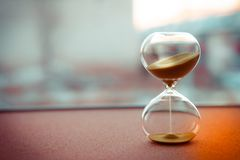 Sand running through the bulbs of an hourglass measuring the passing time in a countdown to a deadline, on a blur background stock photo