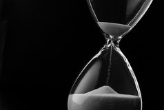 Sand running through the bulbs of an hourglass. Measuring the passing time in a countdown to a deadline, on a dark background with copyspace stock photos