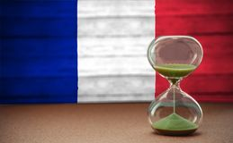 Sand running through the bulbs of an hourglass measuring the passing time in a countdown to a deadline, on France flag background. With copy space royalty free stock photo