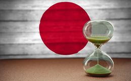 Sand running through the bulbs of an hourglass measuring the passing time in a countdown to a deadline, on Japan flag background. With copy space stock images