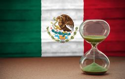 Sand running through the bulbs of an hourglass measuring the passing time in a countdown to a deadline, on mexico flag background. With copy space stock photo