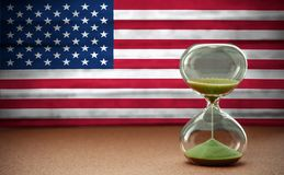 Sand running through the bulbs of an hourglass measuring the passing time in a countdown to a deadline, on USA flag background. With copy space stock images