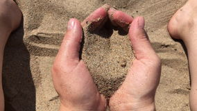 Sand running through cupped hands stock footage
