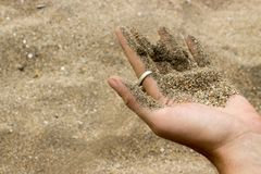 Sand running out from hand at the beach stock photography