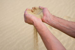 Sand running through hands. Sand falling through the fingers Royalty Free Stock Photos