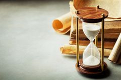 Sand running through the hourglass and old vintage books. Time keeper concept. Sand running through the hourglass and old books. Time keeper concept royalty free stock image