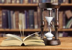 Sand running in hourglass and opened book on. Glass sand hourglass image yellow objects close-up stock photos