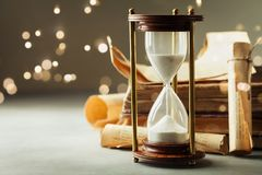 Sand running through the hourglass and old vintage books. Time keeper concept. Sand running through the hourglass and vintage books. Time keeper concept stock photo