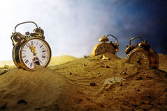Sand running out of an alarm clock, other watches sink into the. Sand running out of a nostalgic alarm clock, other watches sink into the sand, surreal metaphor stock image
