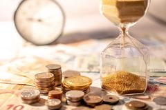 Hourglass and currency on table, Time Investment concept. Sand running through the shape of hourglass on table with banknotes and coins of international currency Stock Photography