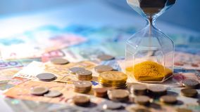 Hourglass and currency on table, Time Investment concept. Sand running through the shape of hourglass on table with banknotes and coins of international currency royalty free stock photos