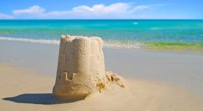 Sand-Schloss durch schönen Ozean Stockbild