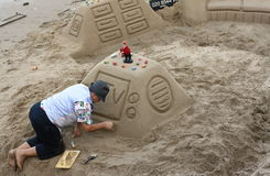 Sand Sculpture. An entertainer creates a sand sculpture of a TV set and living room furniture in the sand revealed at low tide along the South Bank of the River Royalty Free Stock Photo