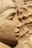 Sand sculpture boy face. Sand sculpture: young man face bas-relief Stock Photos