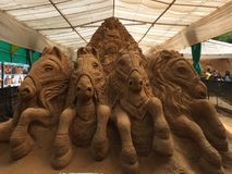 Sand sculpture of a chariot driven by horses. Sand sculpture of a chariot pulled by horses with Lord Krishna as charioteer and Arjun riding on it Stock Image