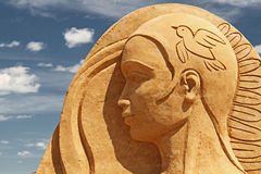 Sand sculpture girl face. Sand sculpture: young woman face with cloudy sky as a background Royalty Free Stock Photo
