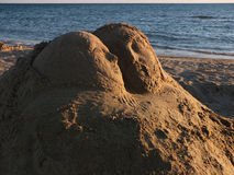 Sand sculpture and the sea Royalty Free Stock Image
