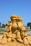 Sand sculpture of Winnie the Pooh. Movie on clear blue sky background Stock Photos