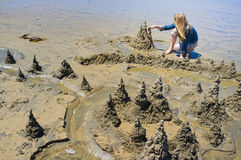 Sand Sculptures, La Jolla Beach, California. A young girl artist with long blond hair in a blue shirt and beige pants builds sculptures of mountains and trees on royalty free stock photos
