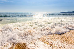 Sand sea beach and blue sky after sunrise and splash of seawater. With sea foam and waves Stock Photo