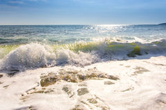 Sand sea beach and blue sky after sunrise and splash of seawater. With sea foam and waves Stock Photos