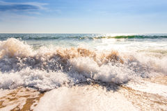 Sand sea beach and blue sky after sunrise and splash of seawater. With sea foam and waves Royalty Free Stock Photos