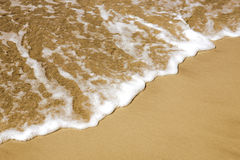 Sand and sea foam Stock Image