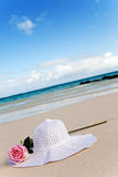 On sand before the sea the rose flower and  hat Stock Image