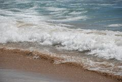 Sand and sea wave on the beach Stock Image