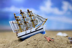 Sand shell and sail in sea Stock Photo