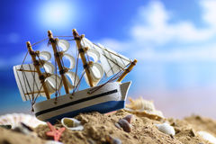 Sand shell and sail in sea Stock Image