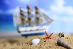 Sand shell and sail in sea Stock Photography