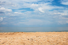 Sand and shelly beach and white clouds over sea. Foreground focus - sand and shelly beach and white clouds over sea. Coastline of Sea of Azov, Temryuk bay Royalty Free Stock Photo