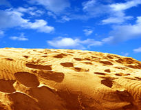 Sand and sky. Vibrant image of cloudy sky and a sand with footprints Royalty Free Stock Image